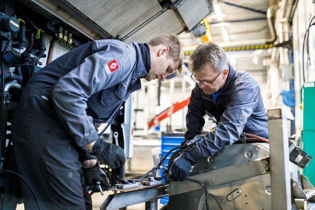 Volvo Trucksi Euroopa president Roger Alm (paremal) aitas maailmameistritiitli võitnud meeskonna ühel liikmel, Lauri Raamatul, välja vahetada Tallinna linnaliinil sõitva hübriidbussi heitgaasipuhasti. Foto: Jarek Jõepera